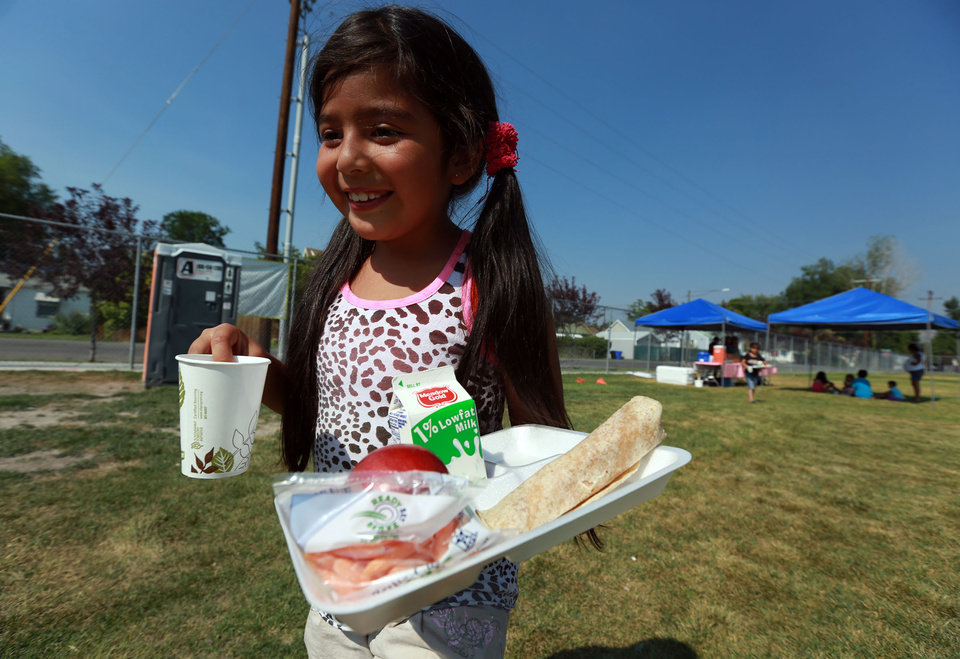 Photo -       Estrella Alba carries her dinner to her car outside of the Central Park Community Center in South Salt Lake on Friday, July 18, 2014. The dinner is part of the Salt Lake CAP summer food program, which offers free dinner to children at five locations in the valley, Monday through Friday.