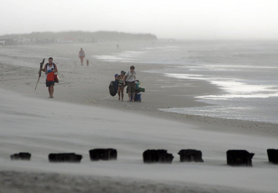 Photo - Clouds and rains move in as beachgoers leave Freeman Park at the north end of Carolina Beach, N.C., Thursday, July 3, 2014. Residents along the coast of North Carolina are bracing for the arrival of the Hurricane Arthur, which threatens to give the state a glancing blow on Independence Day. (AP Photo/Wilmington Star-News, Mike Spencer)