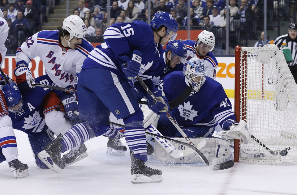 Photo - Toronto Maple Leafs goalie Jonathan Bernier, right, scrambles for the puck with teammates Joffrey Lupul (19), Paul Ranger (15) and Morgan Rielly (44) against New York Rangers' Brian Boyle (22) and J.T. Miller (10) during the first period of an NHL hockey game in Toronto, Saturday, Jan. 4, 2014. (AP Photo/The Canadian Press, Mark Blinch)
