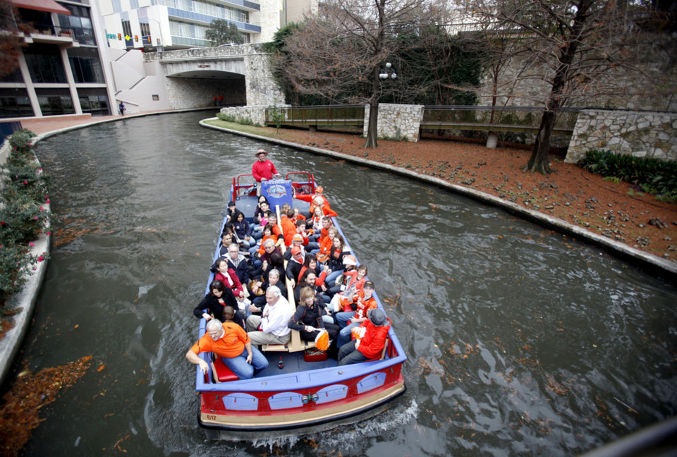 Photo - OSU fans ride a boat on the Riverwalk before the Valero Alamo Bowl college football game between the Oklahoma State University Cowboys and the University of Arizona Wildcats at the Alamodome in San Antonio, Texas, Wednesday, December 29, 2010. Photo by Sarah Phipps, The Oklahoman