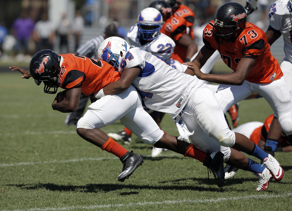 Millwood's Kameron Lyons (64) takes down Douglass's Christopher High (22) during a high school football game between Douglass and Millwood in Oklahoma City, Saturday, Sept. 8, 2012.  Photo by Garett Fisbeck, The Oklahoman