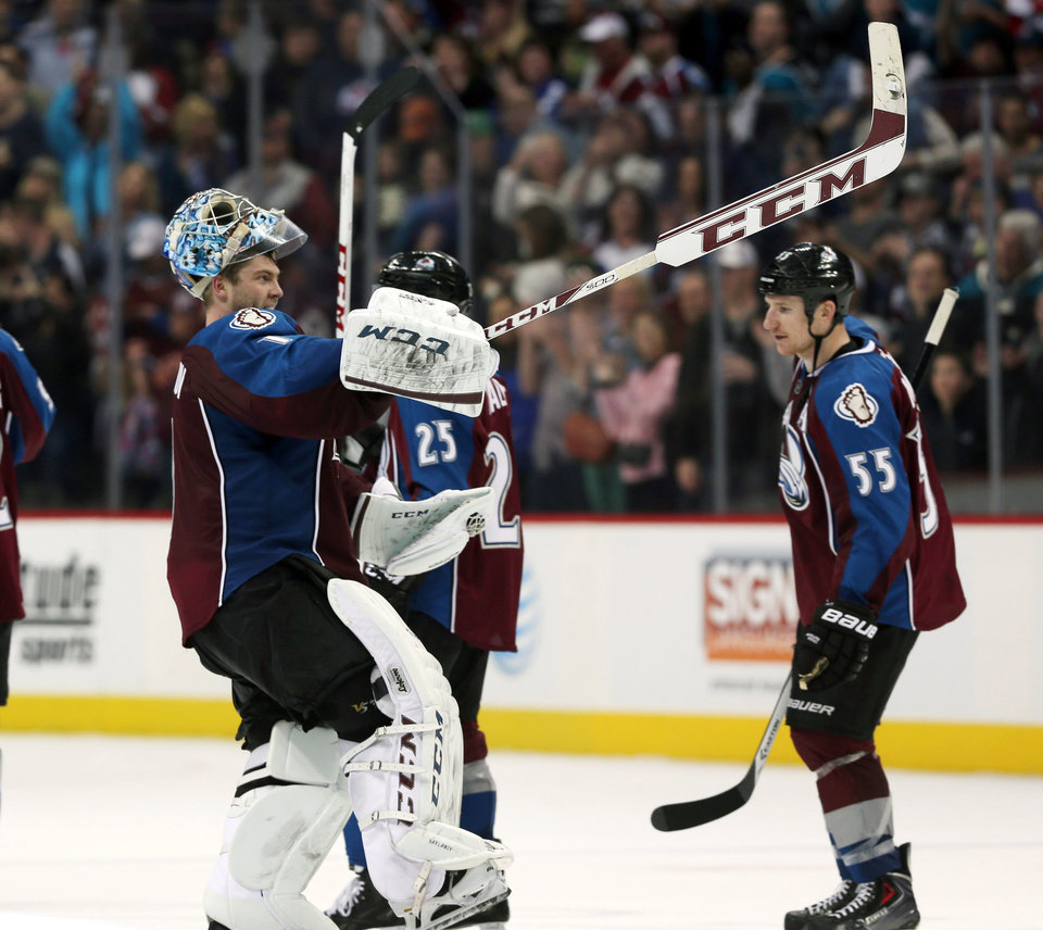 Photo - Colorado Avalanche goalie Semyon Varlamov, front, of Russia, celebrates as left wing Cody McLeod looks on after the Avalanche's 3-2 victory over the San Jose Sharks in an NHL hockey game in Denver on Saturday, March 29, 2014. Varlamov had a season-high 47 saves and the Avalanche clinched their first playoff berth in four years. (AP Photo/David Zalubowski)