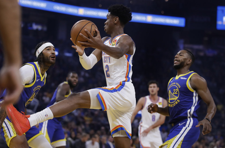 Photo - Oklahoma City Thunder guard Shai Gilgeous-Alexander, center, drives the ball between Golden State Warriors' Willie Cauley-Stein, left, and Glenn Robinson III (22) during the first half of an NBA basketball game Monday, Nov. 25, 2019, in San Francisco. (AP Photo/Ben Margot)