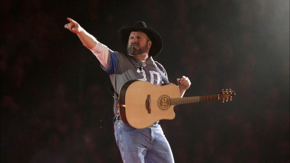 Photo - Garth Brooks sports a Barry Sanders jersey during a concert in Detroit. [DETROIT FREE PRESS]