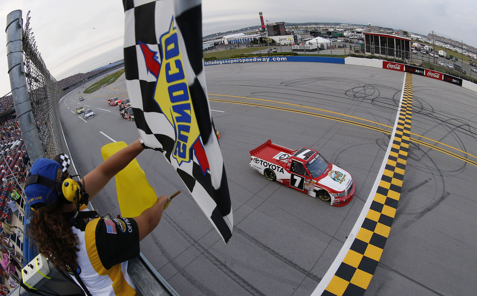 Parker Kligerman takes the checkered and yellow flag to win the NASCAR Camping World Truck Series race at the Talladega Superspeedway in Talladega, Ala., Saturday, Oct. 6, 2012. (AP Photo/Tom Pennington, Pool)