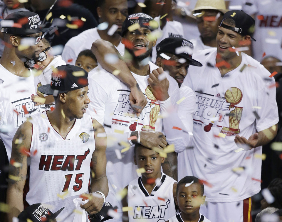 Photo - FILE - In this June 21, 2013 file photo, Miami Heat players including LeBron James, top center, celebrate after Game 7 of the NBA basketball championship game against the San Antonio Spurs, in Miami. As he walked off the court for the final time last season, LeBron James shouted to no one in particular,