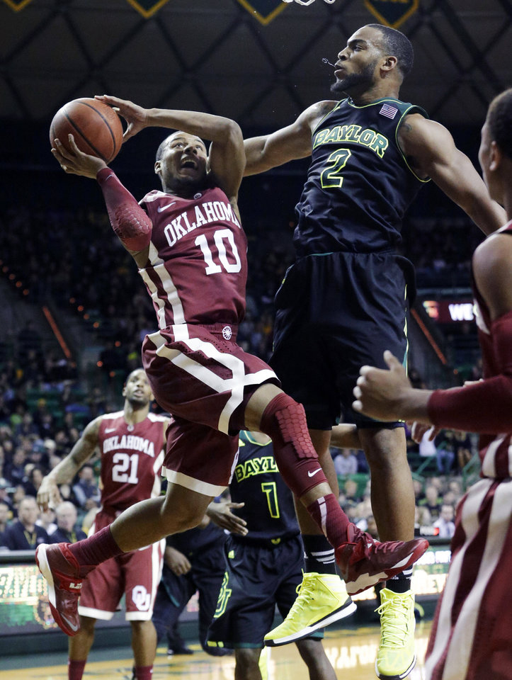 OU�s Jordan Woodard, left, is fouled by Baylor�s Rico Gathers during the Sooners� 66-64 win on Saturday in Waco, Texas. AP Photo