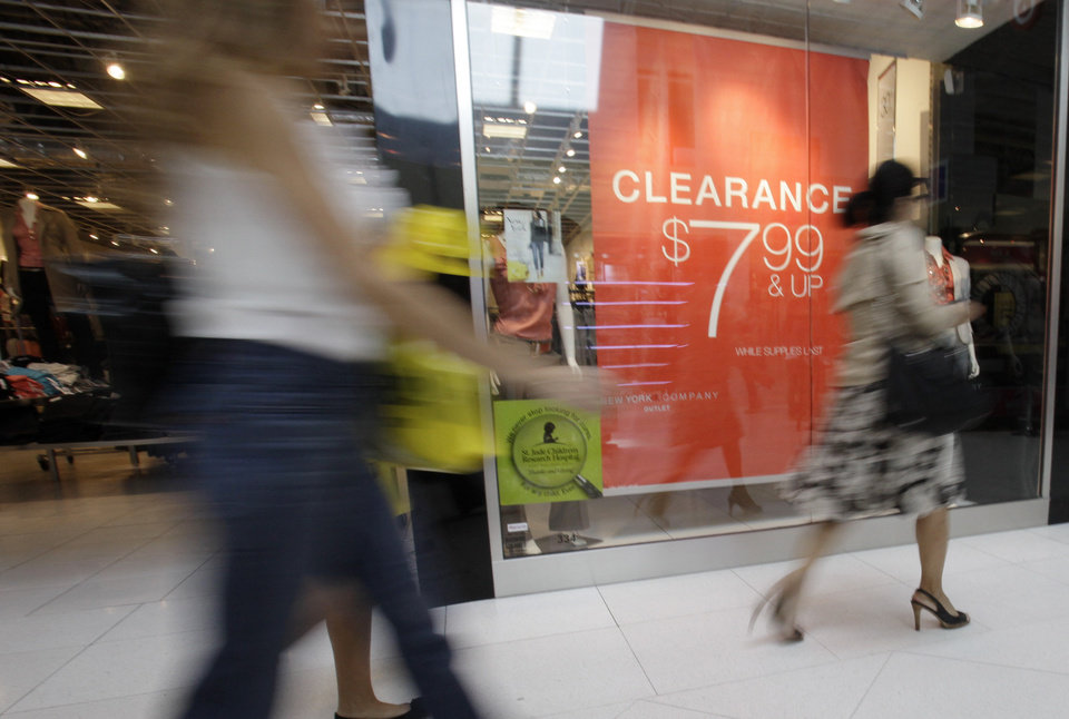Photo -   In this Nov. 9, 2011 file photo, shoppers walk past a clearance sign at the New York & Company outlet store at the Dolphin Mall, in Miami. The economy's recovery looks durable. Hiring, housing, consumer spending and manufacturing all look better but remain less than healthy.(AP Photo/Lynne Sladky, File)