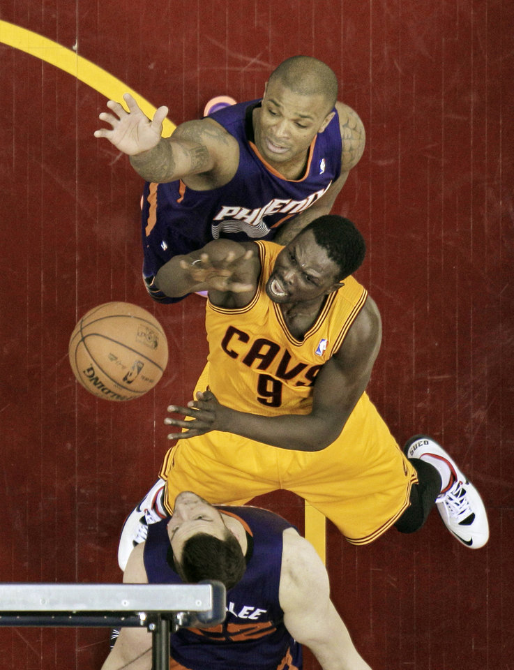 Photo - Cleveland Cavaliers' Luol Deng (9), from Sudan, puts up a shot against Phoenix Suns' P.J. Tucker, top and Miles Plumlee (22) in the first half of an NBA basketball game, Sunday, Jan. 26, 2014, in Cleveland. (AP Photo/Mark Duncan)