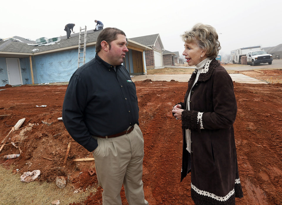 Photo - Jay Kreft, Malarkey Roofing Products plant manager, and Ann Felton Gilliland, chairman and CEO of Central Oklahoma Habitat for Humanity, talk at a house on SE 26 that was the first of many to use roofing materials donated by Malarkey.  NATE BILLINGS - THE OKLAHOMAN