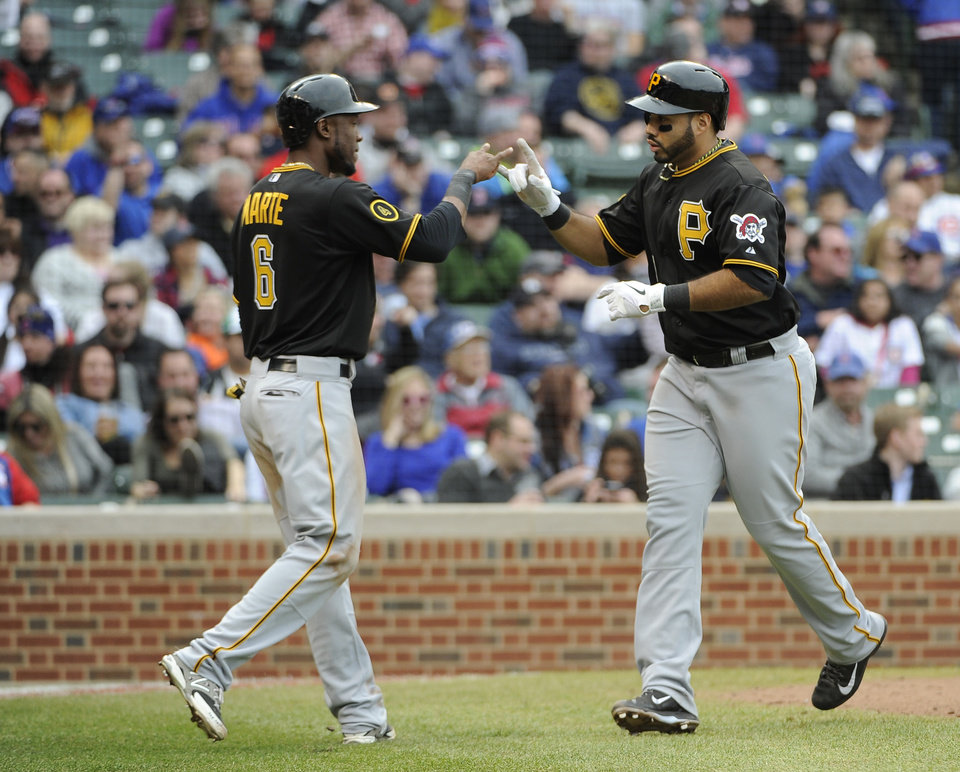 Photo - Pittsburgh Pirates' Pedro Alvarez, right, is greeted by Starling Marte (6) after hitting a three-run home run against the Chicago Cubs during the seventh inning of a baseball game on Thursday, April 10, 2014, in Chicago. (AP Photo/David Banks)