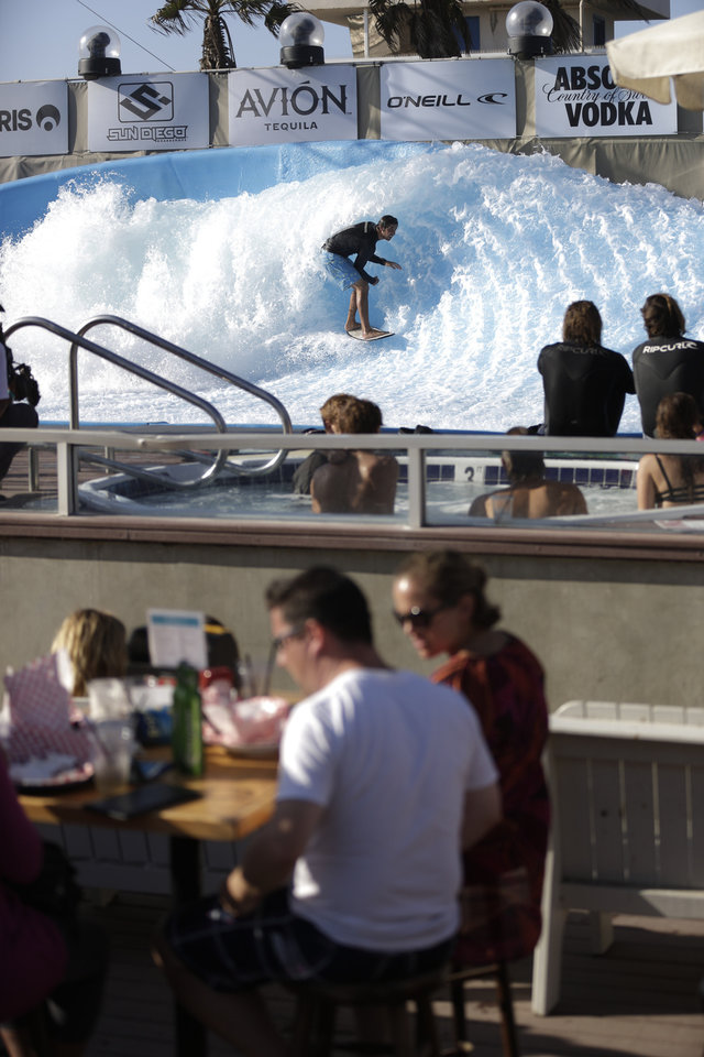 A surfer rides the machine-made wave at Wavehouse San Diego, as others sit at tables Wednesday, Sept. 18, 2013, in San Diego. Surf parks - massive pools with repeating, artificial waves - are the latest buzzword in the surf community. Momentum around surf parks has been growing since the 1960s and but fewer than a dozen serious parks currently exist in locations from Florida to Malaysia _ and cost and wave technology have always been stumbling blocks.  (AP Photo/Gregory Bull)