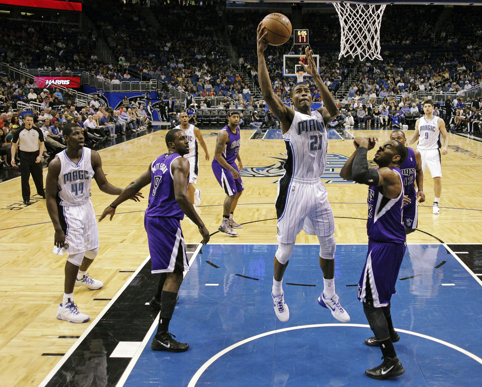 Orlando Magic's Moe Harkless (21) shoots between Sacramento Kings' Patrick Patterson (9) and Marcus Thornton, front right, during the first half of an NBA basketball game, Wednesday, Feb. 27, 2013, in Orlando, Fla. (AP Photo/John Raoux)