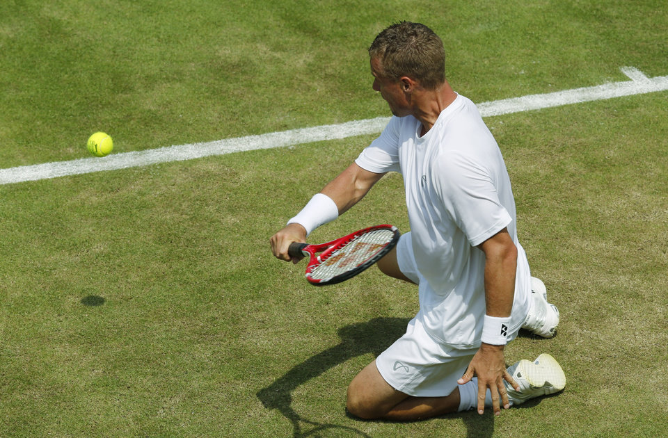Photo - Lleyton Hewitt of Australia plays a shot from his knees to Michal Przysiezny of Poland  during their first round match at the All England Lawn Tennis Championships in Wimbledon, London, Tuesday, June 24, 2014. (AP Photo/Ben Curtis)
