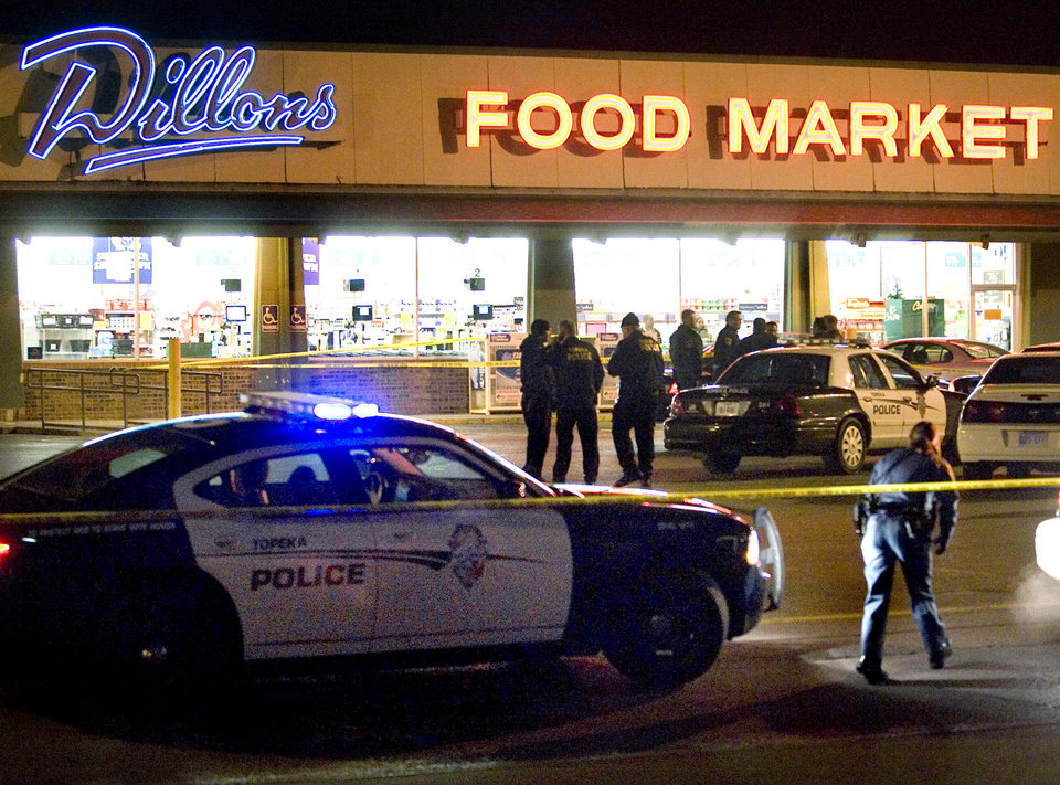 Topeka police investigate at the scene of a shooting outside a grocery store in Topeka, Kan., Sunday, Dec. 16, 2012. Two Kansas police officers were shot outside the store on Sunday while responding to a report of a suspicious vehicle and died later at a hospital, authorities said. (AP Photo/The Topeka Capital Journal, Thad Allton)