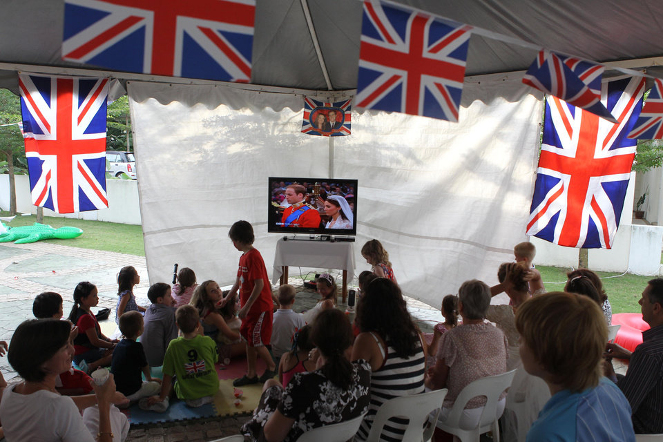 Photo - Supporters of the British royal family watch a TV screen in a suburb of Kuala Lumpur, Malaysia of the Royal Wedding at Westminster Abby in London of Prince William to Kate Middleton, Friday, April 29, 2011. (AP Photo/Mark Baker) ORG XMIT: XMB101