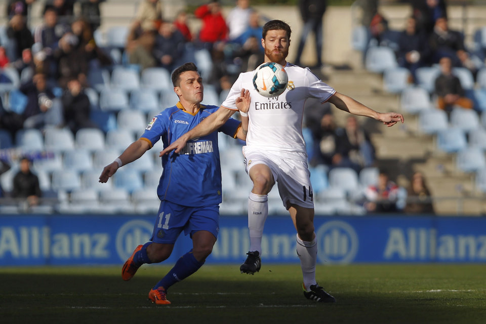 Photo - Real's Xabi Alonso in action with Getafe's Colunga during a Spanish La Liga soccer match between Real Madrid and Getafe at the Coliseum Alfonso Perez stadium in Madrid, Spain, Sunday, Feb. 16, 2014. (AP Photo/Gabriel Pecot)