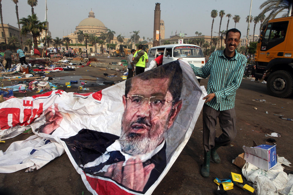Photo - An Egyptian pulls a banner of Egypt's ousted President Mohammed Morsi near debris left at a protest camp in Nahda Square, Giza, Cairo, Egypt, Thursday, Aug. 15, 2013. Egypt faced a new phase of uncertainty on Thursday after the bloodiest day since its Arab Spring began, with over 300 people reported killed and thousands injured as police smashed two protest camps of supporters of the deposed Islamist president. Wednesday's raids touched off day-long street violence that prompted the military-backed interim leaders to impose a state of emergency and curfew, and drew widespread condemnation from the Muslim world and the West, including the United States. (AP Photo/Amr Nabil)
