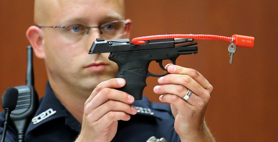 Photo - Sanford police officer Timothy Smith holds up the gun that was used to kill Trayvon Martin, while testifying in the 15th day of the George Zimmerman trial, in Seminole circuit court in Sanford, Fla., Friday, June 28, 2013. Zimmerman has been charged with second-degree murder for the 2012 shooting death of Trayvon Martin.(AP Photo/Orlando Sentinel, Joe Burbank, Pool)