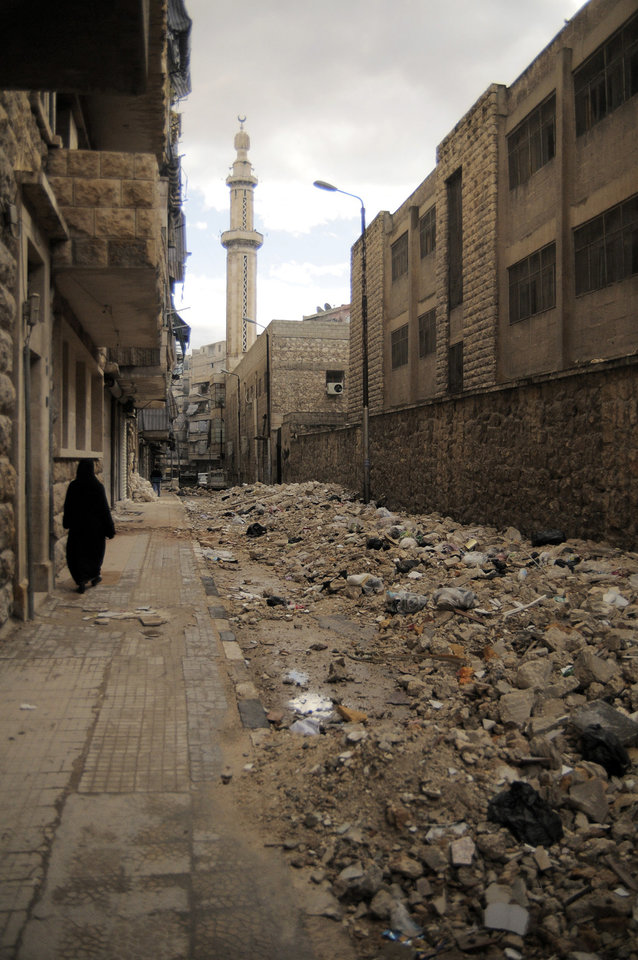Photo -   In this Saturday, Nov. 10, 2012 photo, a women passes near rubble and garbage in the Al-Bohout area of Aleppo, Syria. Due the heavy fighting and shelling, the garbage collection system collapsed weeks ago. (AP Photo/Mónica G. Prieto)