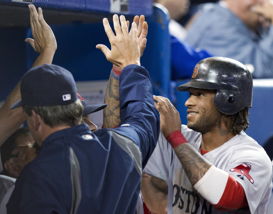 Photo -   Boston Red Sox pinch-runner Darnell McDonald is congratulated by teammates after scoring against the Toronto Blue Jays during the ninth inning of a baseball game in Toronto on Monday, April 9, 2012. (AP Photo/The Canadian Press, Frank Gunn)