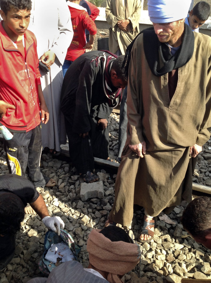 Photo -   Egyptians gather body parts at the scene of a train crash that killed at least 47 people, most of them children near Assiut in southern Egypt, Saturday, Nov. 17, 2012. As one man picked up a body part he screamed: