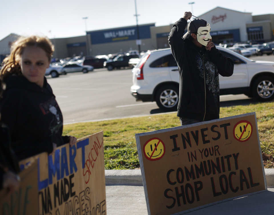 Jenny Dollar and Rob Shawnee stand with signs during an Occupy OKC demonstration at a Wal-Mart in Del City, Friday, Nov. 23, 2012. Members of the Occupy movement were protesting for Wal-Mart worker\'s rights to a living wage. Photo by Garett Fisbeck, The Oklahoman