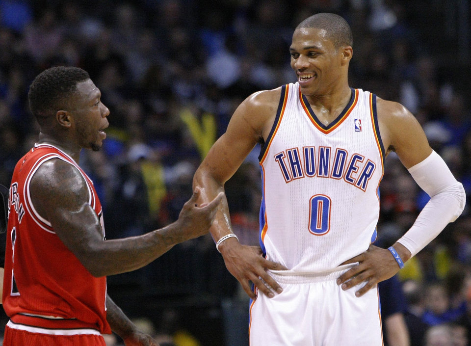 Chicago Bulls Nate Robinson, left, and Oklahoma City Thunder guard Russell Westbrook, right, talk during a time out in the third quarter of a NBA basketball game in Oklahoma City, Sunday, Feb. 24, 2013.  Oklahoma City won 102-72.  (AP Photo/Alonzo Adams)