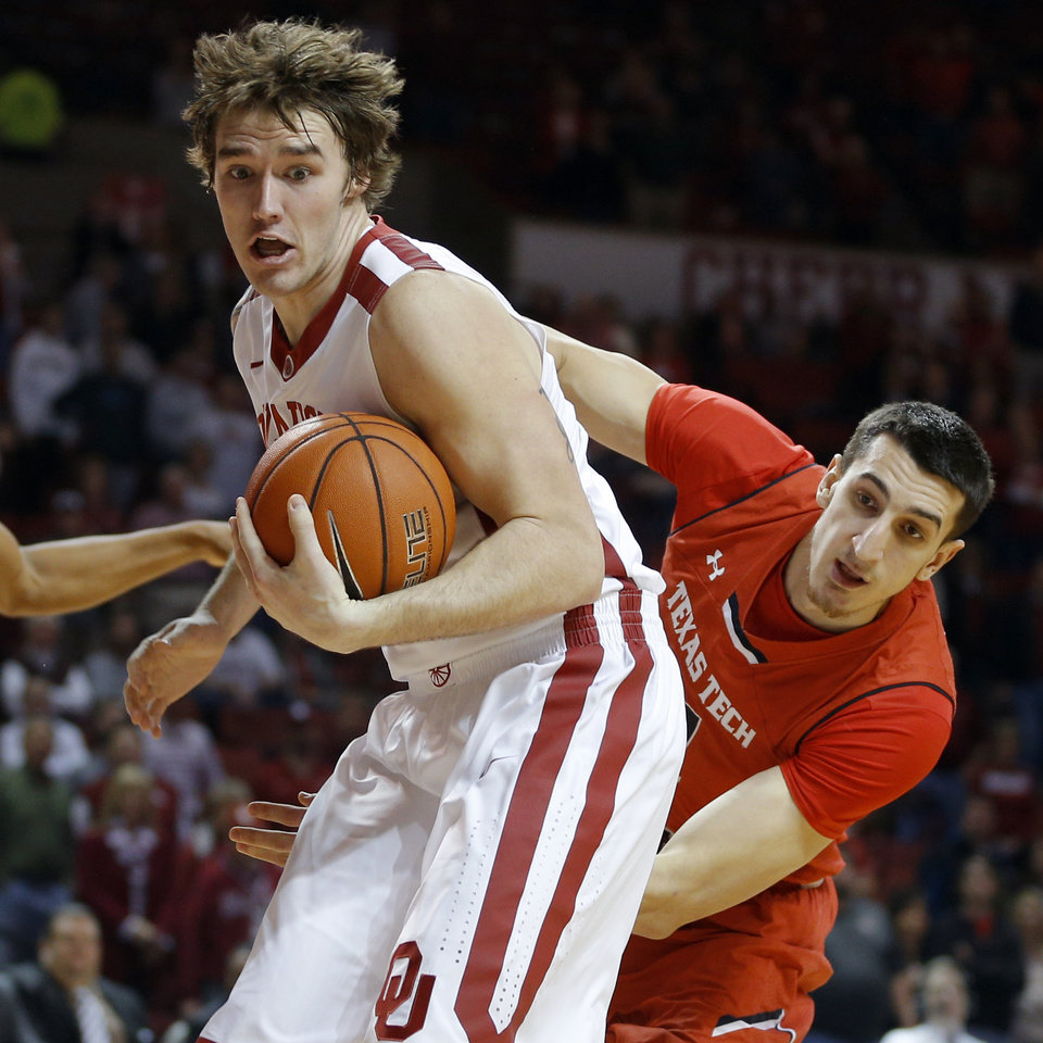 Photo - Oklahoma's Ryan Spangler (00) grabs the ball in front of Texas Tech's Dejan Kravic (11) during an NCAA college basketball game between the University of Oklahoma and Texas Tech University at the Lloyd Noble Center in Norman, Okla., Wednesday, Feb. 12, 2014. Photo by Bryan Terry, The Oklahoman