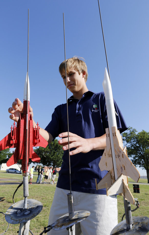 Photo -  Jacob Mace, 15, prepares his rocket for launch June 11 during Sooner Flight Academy in Norman. Photo by Steve Sisney, The Oklahoman      -