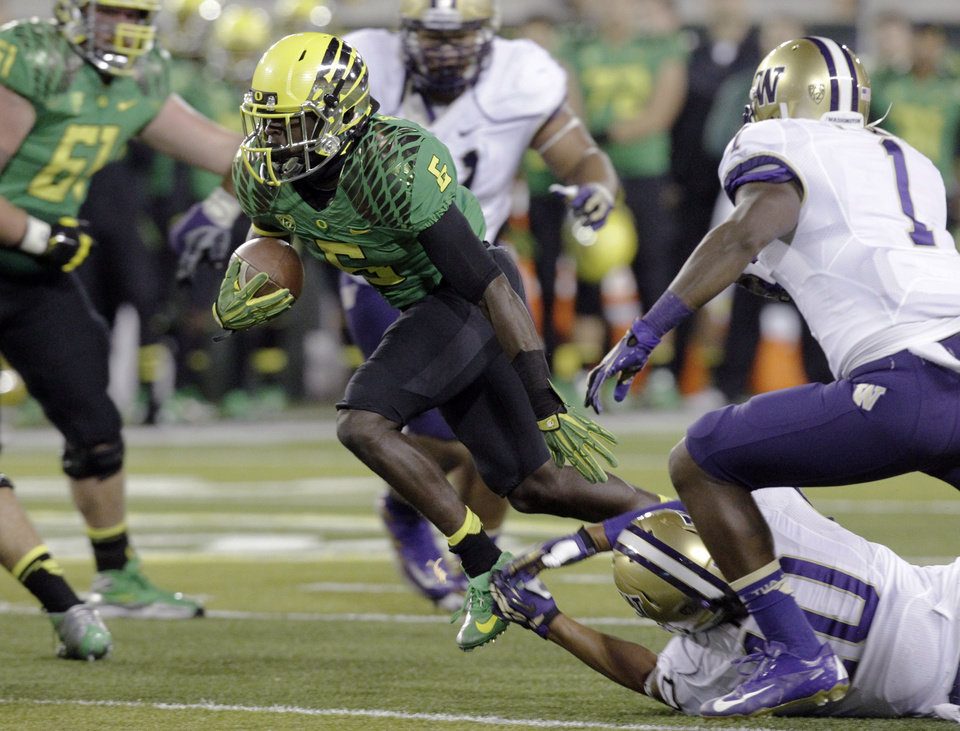 Oregon running back De'Anthony Thomas (6) breaks through Washington's defensive secondary, including Sean Parker (1) and John Timu (10), on his way to a touchdown during the first half of an NCAA college football game in Eugene, Ore., Saturday, Oct. 6, 2012. (AP Photo/Don Ryan)