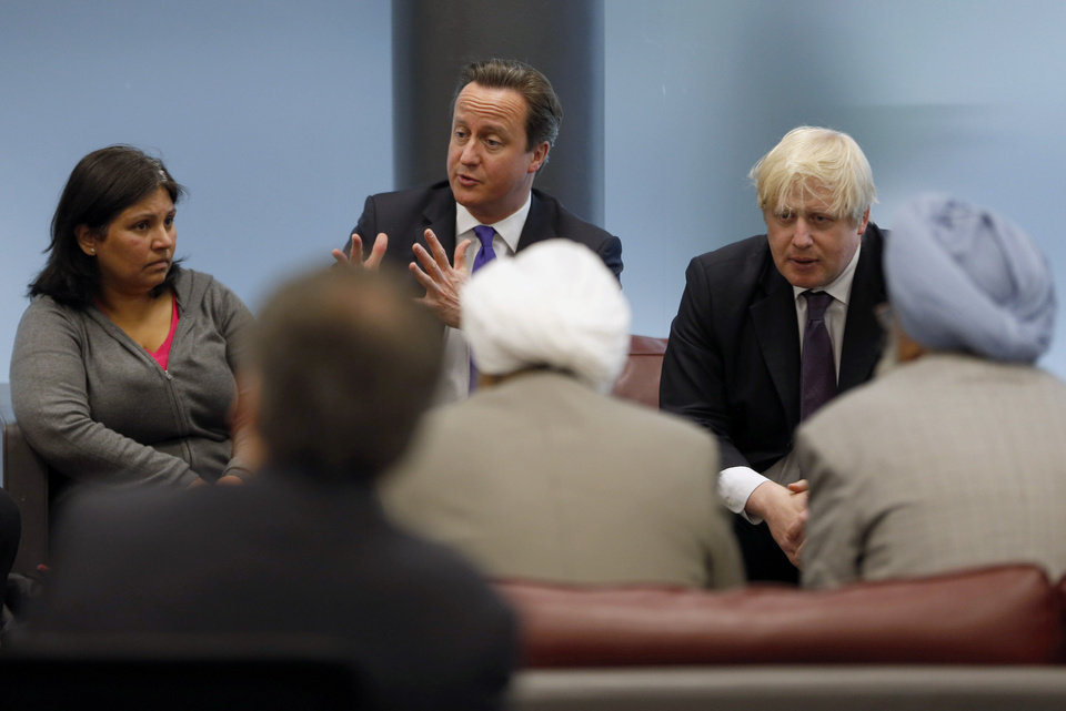 Photo - British Prime Minister David Cameron, centre,  and London Mayor Boris Johnson, right,  speak to members of the local community, Thursday, May 23, 2013, during a visit to Woolwich, southeast London where an attack took place on Wednesday. Britain was coming to terms with an apparent return of terrorism to its capital Thursday as new information emerged about the killing of a British soldier near an army barracks in Woolwich by suspected Islamic radicals. (AP Photo/Sang Tan, Pool)