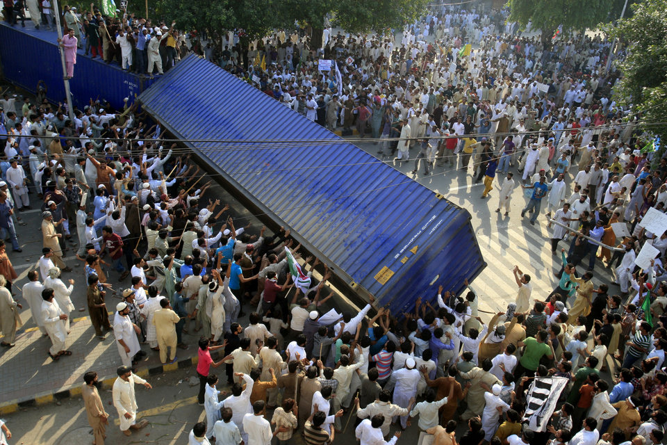 "Pakistani protesters topple a shipping container police used to block the road to the US consulate in Lahore, Pakistan on  Friday, Sept 21, 2012. Tens of thousands protested around the country against an amateurish anti-Muslim film produced in the United States and vulgar caricatures of the Prophet Muhammad published in a French satirical weekly after the government encouraged peaceful protests and declared a national holiday — ""Love for the Prophet Day."" Demonstrations turned violent in several Pakistani cities and over a dozen people were killed and many more injured. AP photo"