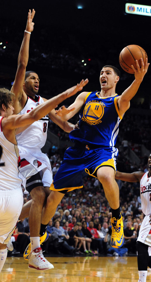 Photo - Golden State Warriors guard Klay Thompson (11) drives to the basket on Portland Trail Blazers forward Nicolas Batum (88) during the first half of an NBA basketball game in Portland, Ore., Sunday, April 13, 2014. (AP Photo/Steve Dykes)