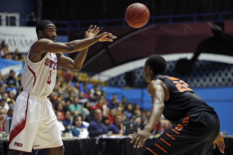 Oklahoma State's Markel Brown, right, pressures NC State's Rodney Purvis during a NCAA college basketball game in Bayamon, Puerto Rico, Sunday, Nov. 18, 2012. (AP Photo/Ricardo Arduengo)