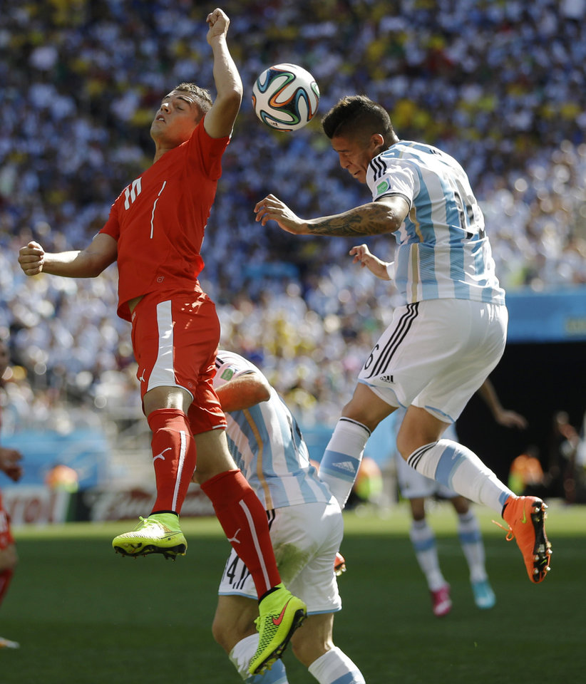 Photo - Argentina's Marcos Rojo, right, and Switzerland's Granit Xhaka go for a header during their World Cup round of 16 soccer match at the Itaquerao Stadium in Sao Paulo, Brazil, Tuesday, July 1, 2014. (AP Photo/Kirsty Wigglesworth)