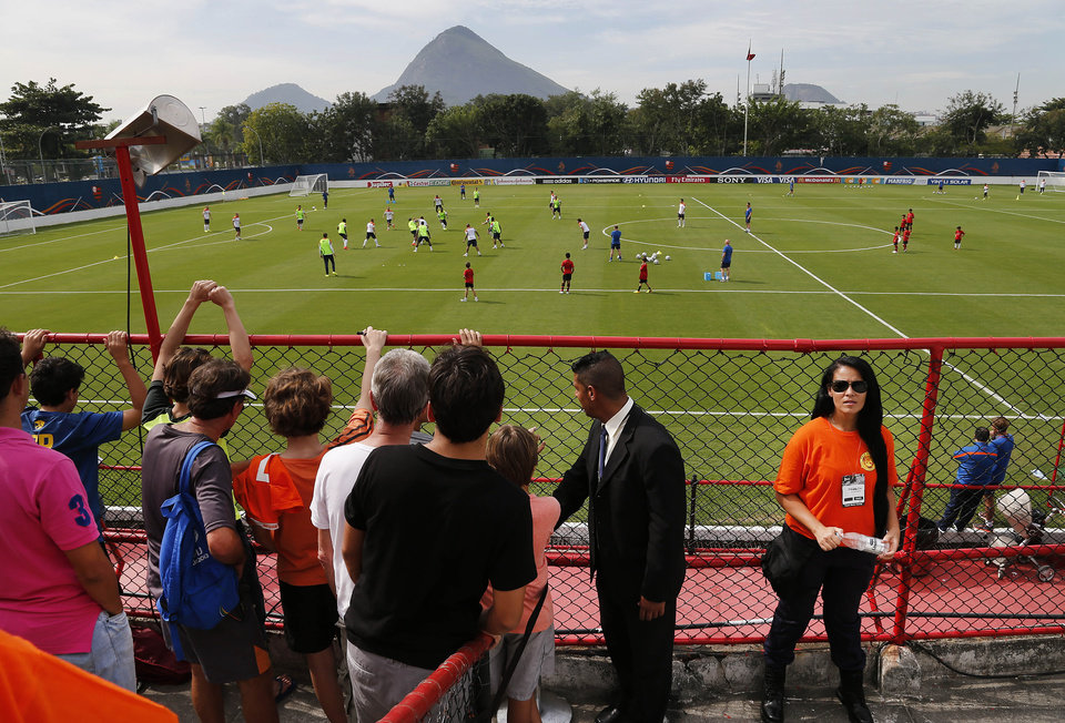 Photo - Fans of the Netherlands soccer team and a security personnel, right, are dressed in splashes of the national colour orange as they watch from the stands during a training session in Rio de Janeiro, Brazil, Saturday, June 7, 2014.  The colour orange is an ancient symbol of the Dutch royal family and is widely used as a mark of national pride.  The Netherlands had their first training session open to fans at the Brazilian club Flamengo training complex. The Netherlands plays in group B of the 2014 soccer World Cup. (AP Photo/Wong Maye-E)