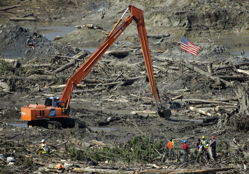 A group of workers stands near a long-arm excavator and a U.S. flag Tuesday, April 1, 2014, near Darrington, Wash., as work continued to search for victims of the deadly mudslide that hit the community of Oso,Wash. on March 22, 2014. Officials said the excavator was helping them reach deep pools of of water or other muddy areas that had been difficult to search in the past. (AP Photo/Ted S. Warren)