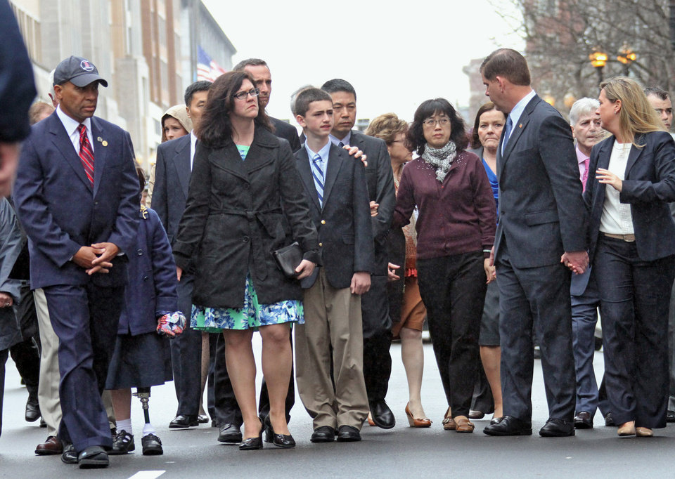 Photo - Massachusetts Gov. Deval Patrick, left, along with the Richard family and family members of Lingzi Lu walk with Boston Mayor Marty Walsh, second from right, as they attend ceremonies to commemorate the one year anniversary of the Boston Marathon bombings, Tuesday, April 15, 2014, in Boston. Martin Richard lost was killed in the bombing. (AP Photo/The Boston Herald, Nancy Lane)  BOSTON GLOBE OUT; METRO BOSTON OUT; MAGS OUT; ONLINE OUT