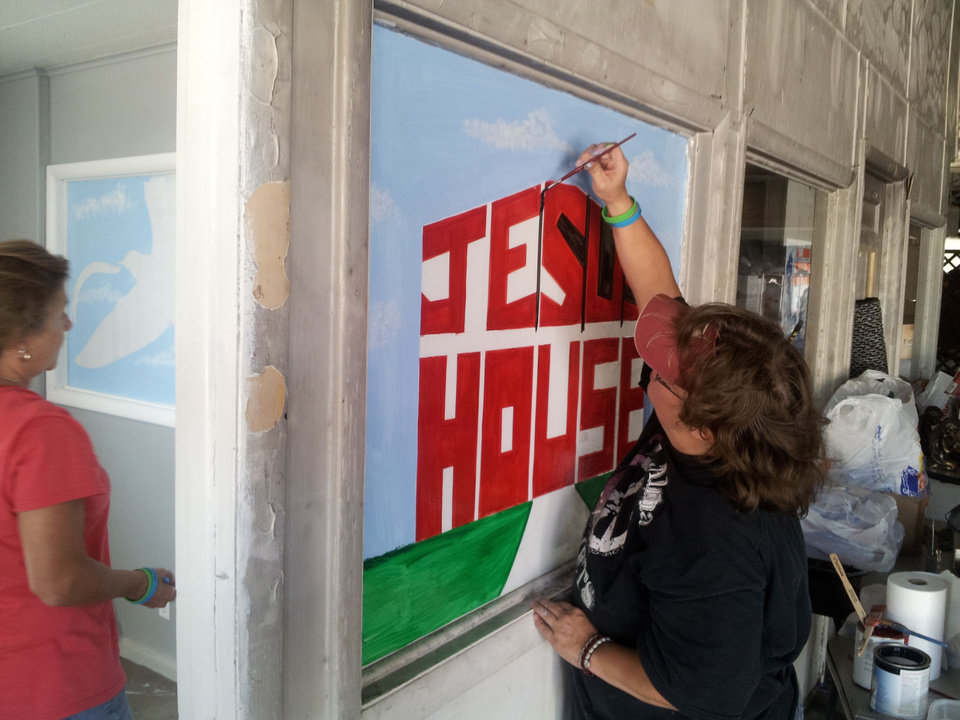 Debbie Richardson, a graphic artist and Velma Police officer, paints the Jesus House logo on a window as part of a refurbishment project targeting the Jesus House prayer room. Photo provided <strong></strong>