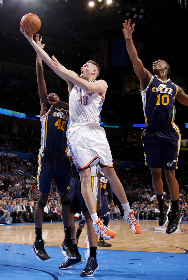 Photo - Oklahoma City's Cole Aldrich (45) goes between Utah's Jeremy Evans (40) and Alec Burks (10) during an NBA game between the Oklahoma City Thunder and the Utah Jazz at Chesapeake Energy Arena in Oklahoma CIty, Tuesday, Feb. 14, 2012. Photo by Bryan Terry, The Oklahoman