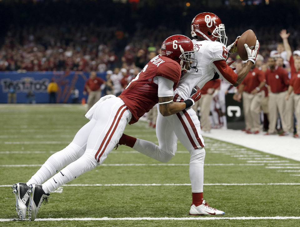 Photo - Oklahoma's Jalen Saunders (8) makes a catch Alabama's Ha Ha Clinton-Dix (6) tries to bring him down during the NCAA football BCS Sugar Bowl game between the University of Oklahoma Sooners (OU) and the University of Alabama Crimson Tide (UA) at the Superdome in New Orleans, La., Thursday, Jan. 2, 2014. Photo by Sarah Phipps, The Oklahoman