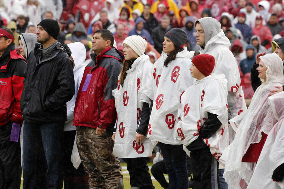 Photo - Members of the Winchester family stand at midfield before the Bedlam college football game between the Oklahoma Sooners (OU) and the Oklahoma State Cowboys (OSU) at Gaylord Family - Oklahoma Memorial Stadium in Norman, Okla., Saturday, Dec. 3, 2016. Photo by Steve Sisney, The Oklahoman