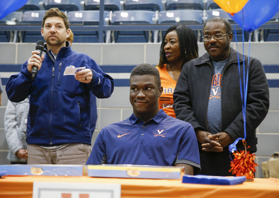 Photo - Daryl Dike, middle, listens to Edmond North soccer coach Chris Waugh, left, talk about him with his parents, Jessy Dike and Vincent Dike, during a ceremony for National Signing Day at Edmond North High School in Edmond, Okla., Wednesday, Feb. 7, 2018. Dike signed to play soccer at Virginia. Photo by Nate Billings, The Oklahoman