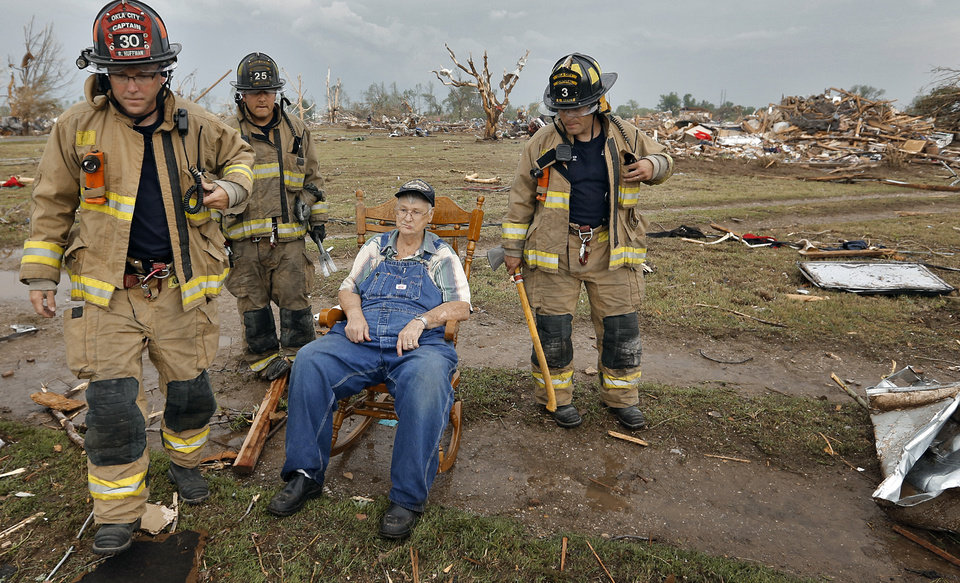 Photo - Oklahoma City firefighters check on the status of Gene Tripp as he sits in his rocking chair where his home once stood after being destroyed by a tornado that hit the area, Monday, May 20, 2013 in Oklahoma City, Okla. (AP Photo/The Oklahoman, Chris Landsberger)