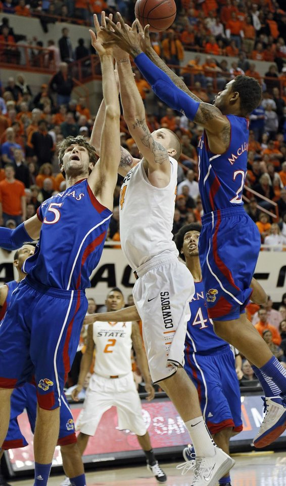 Photo - Oklahoma State 's Philip Jurick (44) battles fort a rebound with Kansas' Jeff Withey (5) and Ben McLemore (23) during the college basketball game between the Oklahoma State University Cowboys (OSU) and the University of Kanas Jayhawks (KU) at Gallagher-Iba Arena on Wednesday, Feb. 20, 2013, in Stillwater, Okla. Photo by Chris Landsberger, The Oklahoman