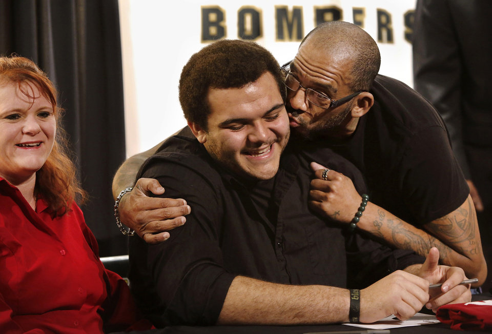 Photo - Carlos Freeman, Sr. playfully kisses his son, Midwest City High School offensive lineman Carlos Freeman, after he  signed his name to a letter of intent to play football at Washington State University during a  ceremony with fellow Bomber players in the school's performing arts building on Wednesday, Feb. 6, 2013.  Laughing at the father and son antics is his mom,  Kim Lowe.  Photo by Jim Beckel, The Oklahoman