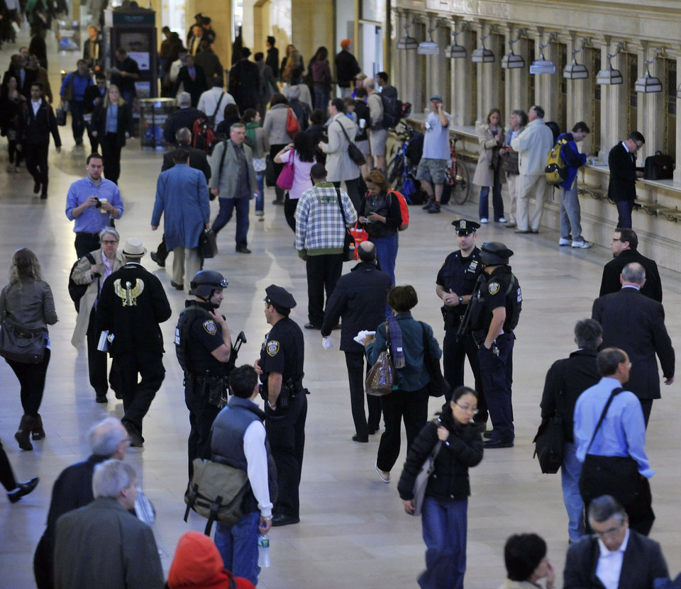 Photo - Armed Metropolitan Transportation Authority police officers and city police officer stand among the travelers in New York's Grand Central Station on  Monday, May 2, 2011. Security was heightened as a result of the announcement of the killing of Osama Bin Laden. (AP Photo/Stephen Chernin)