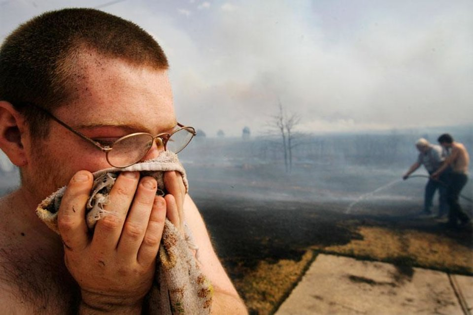 John Brewer holds a wet towel to his face after battling wildfires in his housing addition in Midwest City, Okla., Thursday, April 9, 2009.  Photo by Jim Beckel, The Oklahoman