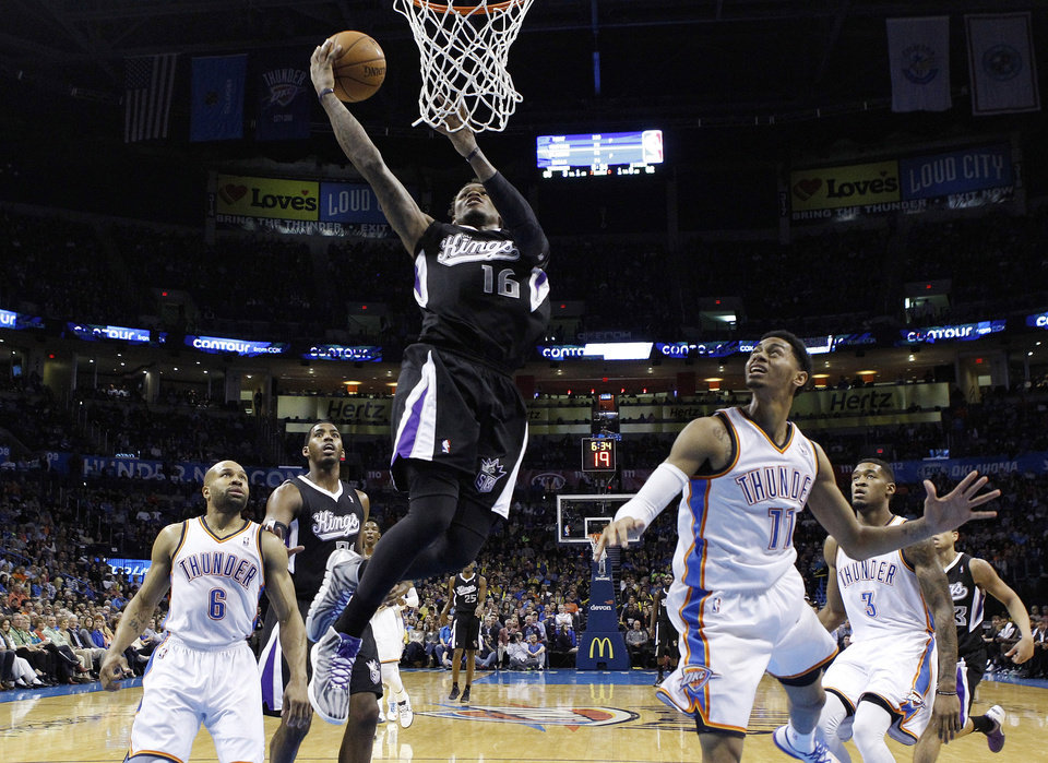 Photo - Sacramento Kings guard Ben McLemore (16) shoots between Oklahoma City Thunder guard Derek Fisher (6) and guard Jeremy Lamb (11) during the fourth quarter of an NBA basketball game in Oklahoma City, Friday, March 28, 2014. Oklahoma City won 94-81. (AP Photo/Sue Ogrocki)